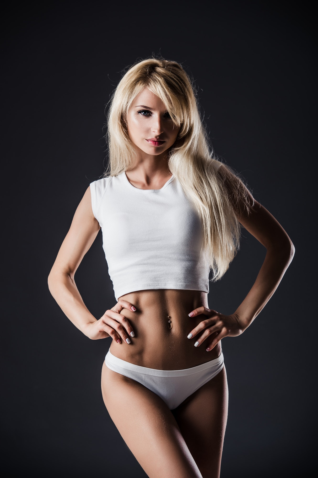 Fitness blonde woman shows her body. Fitness motivation. Perfect female sports figure. Fitness woman
